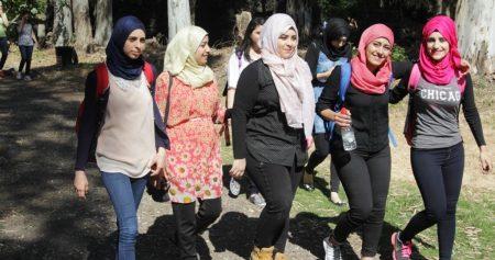 Five Arab women college students walking across campus