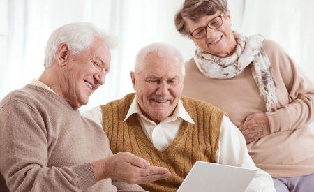 Three seniors looking at a computer screen