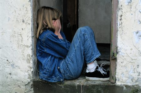 Young girl sitting in a doorstep with her hands over her face