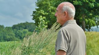 elderly man looking out at field