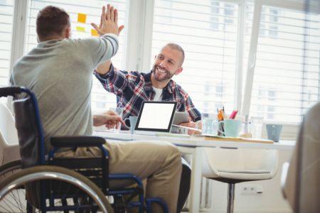 Man in wheel chair high-fiving his friend